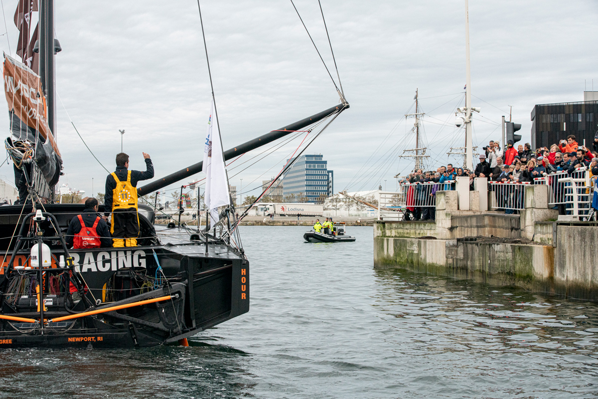 Charlie enright waves to fans as the 11th hour racing team leaves for the start of the transat jacques vabre